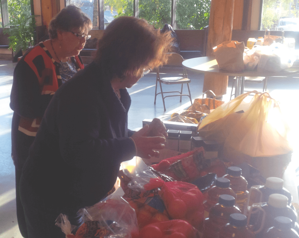 Deborah Randall and Gracie Karp preparing Thanksgiving baskets